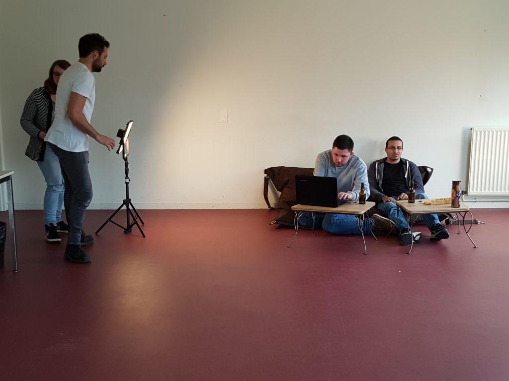 Un technicien de l'association AMPAR installe la lumière pendant que deux des membres d'HandiSup participant au tournage sont installés dans des pouffes de la Maison des Étudiants