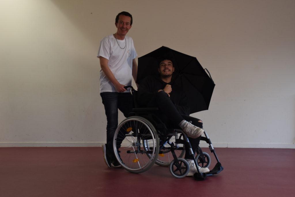 Mathieu (assis dans un fauteuil roulant) et Nicolas (se tenant debout derrière lui) se préparant au tournage du premier spot vidéo.